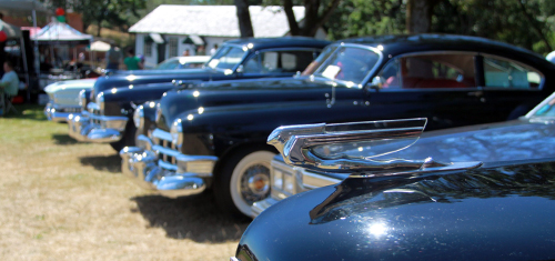 Close up of four black Cadillac on display