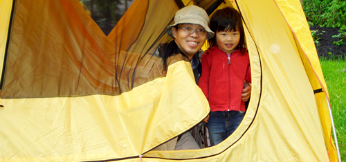 – A parent and 3 year-old daughter pocking through the yellow tent door