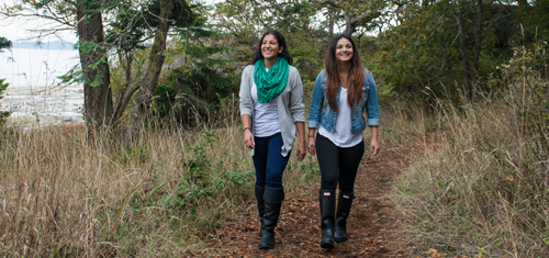 Two young ladies walking on a shoreline nature trail