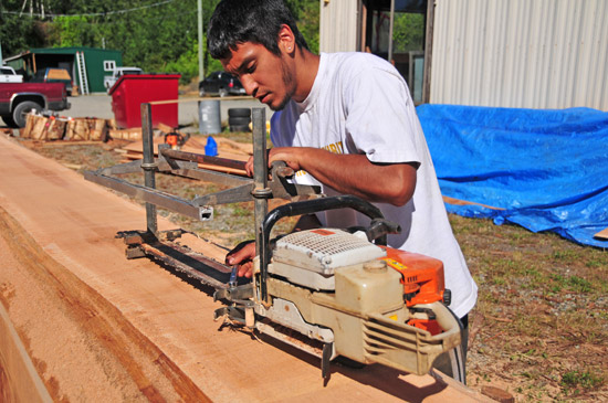 Carving assistant Tyler York uses an Alaska mill to shape the log