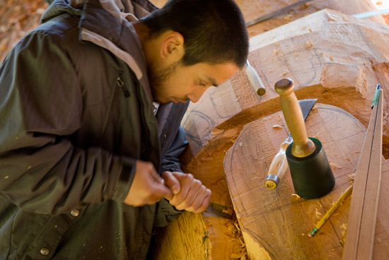 Carving assistant Tyler York carves out the major forms on the pole.