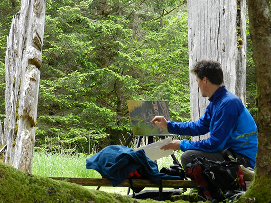 Charlie takes a snapshot of the poles at SGang Gwaay, in acrylic paint