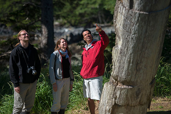Three adults stand as a Haida Gwaii Watchmen points to remnants of a village site