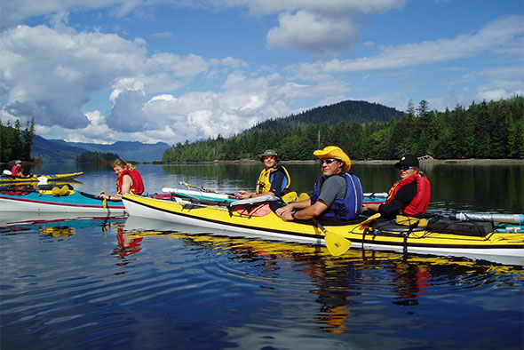 A group of kayakers come together on a calm waterway on a sunny day