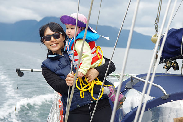 A smiling woman holding a child stands on a sailboat
