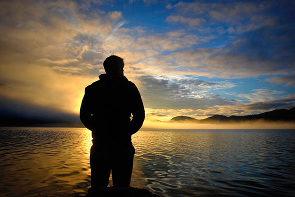 A man stands in front of a sunrise, looking over the calm water as mist burns off