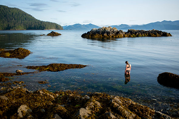 A woman stands knee deep in the water on a rocky coastline