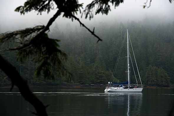 A sailboat motors on calm water under a low cloud layer