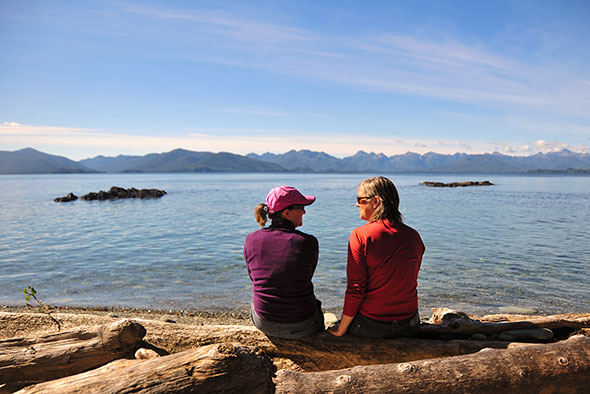 Two women talk to each other while sitting on a log overlooking a calm inlet