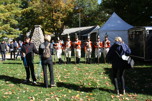 Military re-enactors in period costume standing in front of an 1812 On Tour tent  while members of the public take photos at Queenston Heights in Queenston, Ontario