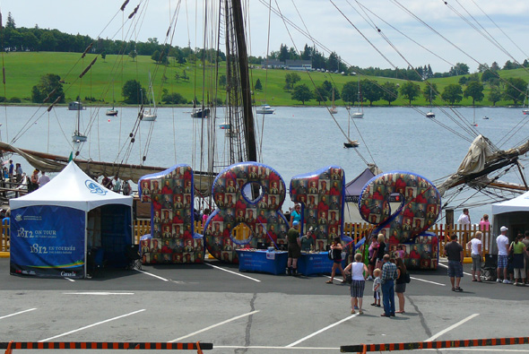 1812 On Tour tents and huge inflatable 1812 numbers with a tall ship in the background