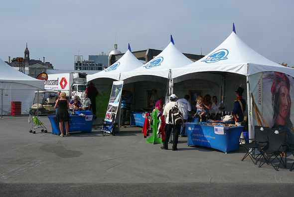 1812 On Tour staff, inside tents, welcome the public at the Montréal Tall Ships Festival