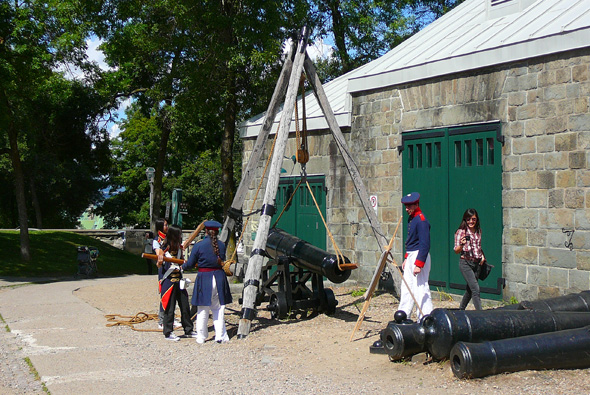 Interperters in period costume mounting a cannon at the Artillery building
