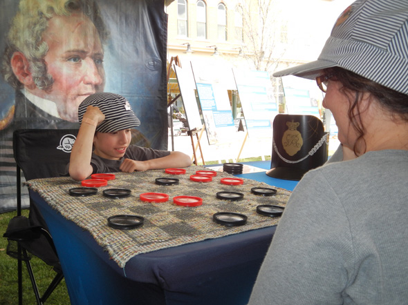 A boy plays a game of checkers with an 1812 On Tour staff member at the Heritage Park Historical Village in Calgary, Alberta, 2013