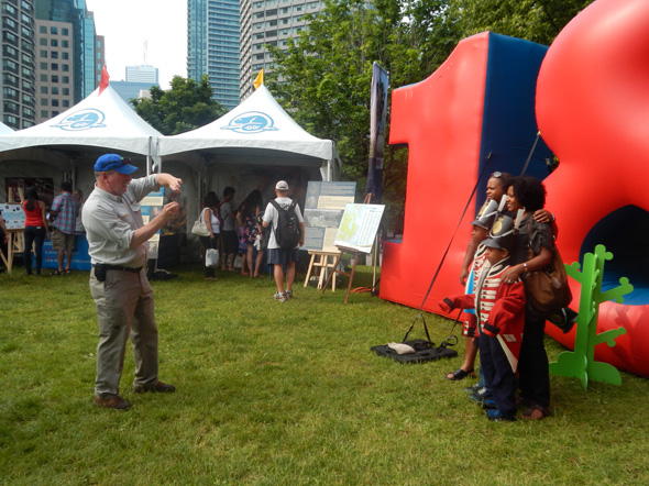 A family is having their photo taken in front of the large 1812 inflatable at the Redpath Waterfront Festival – Tall Ships 1812 Tour, in Toronto, Ontario, 2013