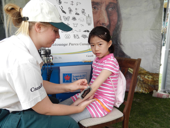 A girl receives a tattoo while visiting the 1812 On Tour kiosk at the Heritage Park Historical Village in Calgary, Alberta, 2013