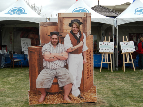 A young couple poses for a fun photo in front of the 1812 On Tour tents at the Heritage Park Historical Village in Calgary, Alberta, 2013