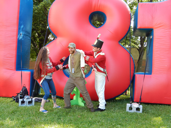 A young couple tries on  military coats  in front of the large inflatable 1812  number at the Redpath Waterfront Festival – Tall Ships 1812 Tour, in Toronto,  Ontario, 2013