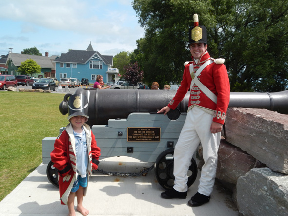 Parks Canada interpreter posing with a little boy dressed as a War of 1812 British soldier in Gananoque, Ontario, 2013