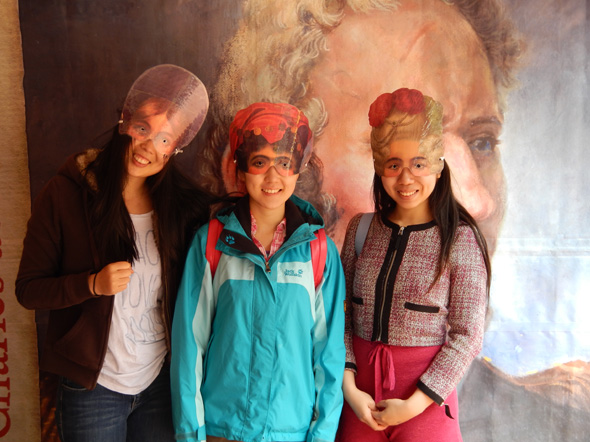 Three girls try on masks at the 1812 On Tour kiosk while visiting Cave and Basin National Historic Site in Banff, Alberta, 2013