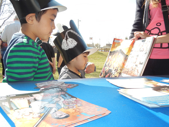 Two young brothers read about the War of 1812 at the 1812 On Tour kiosk at The Forks National Historic Site in Winnipeg, Manitoba, 2013