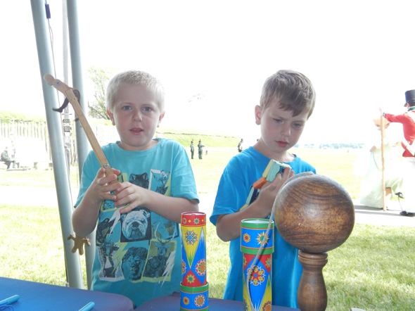 Two young boys play with replica 19th-century toys at the 1812 On Tour kiosk at Fort Wellington National Historic Site in Prescott, Ontario, 2013