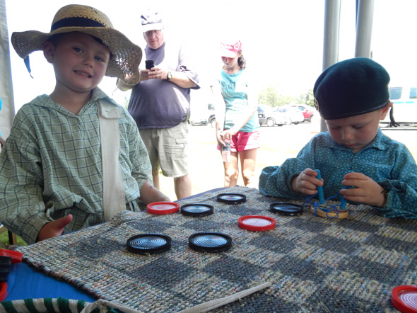Two little brothers play checkers at the 1812 On Tour kiosk in Morrisburg, Ontario, 2013