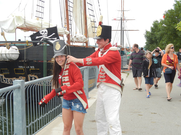 An 1812 On Tour interpreter dressed as a British soldier helps a visitor try on a red coat at the Tall Ships Festival in Hamilton, Ontario, 2013
