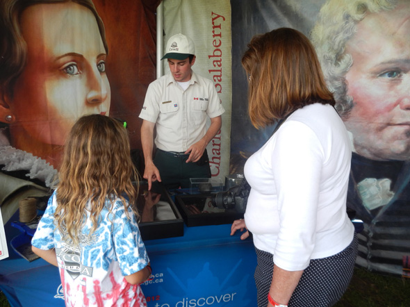 Visitors look at a 200-year-old bayonet at the 1812 On Tour kiosk during the Tall Ships Festival in Hamilton, Ontario, 2013