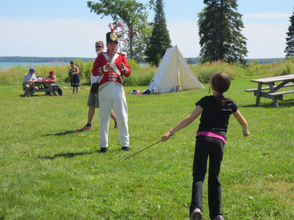 An 1812 On Tour interpreter dressed as a British soldier plays the Game of Grace with a young girl on St. Joseph Island, Ontario, 2013