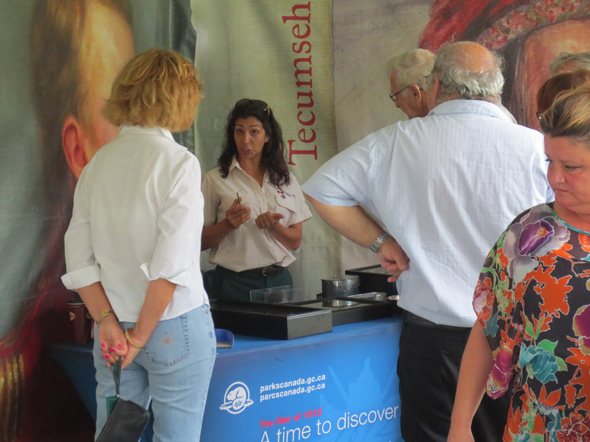 Guide explaining artifacts to visitors at the 1812 On Tour kiosk in Windsor, Ontario, 2013