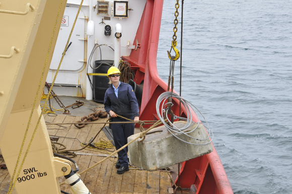 Deckhand Tess Szostakiwskyj helps belay a navigation buoy's concrete anchor during buoying operations.