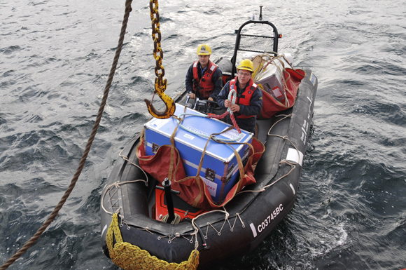 Leading Seaman Kurt Westle (left) and Seaman Ronald John ferrying ROV and survey gear to the ship's forward hold.