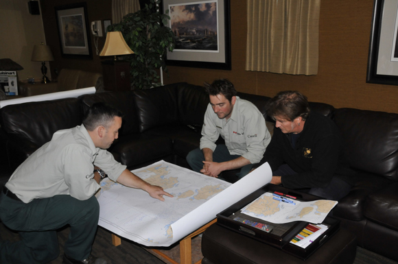 Jonathan Moore, Ryan Harris and Hydrographer in Charge Andrew Leyzack during a final discussion of the 2011 search area.
