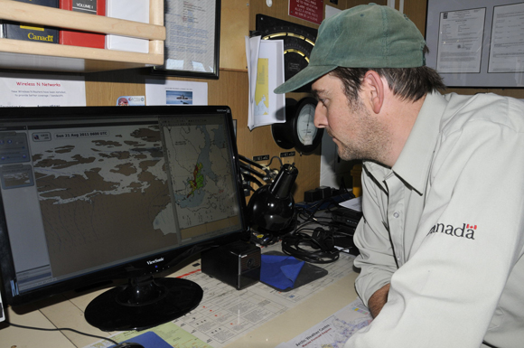 Ryan Harris from Parks Canada's Underwater Archaeology Service studies the ice conditions in anticipation of the pending survey.