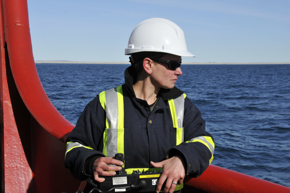 Boatswain Peter Lange directs the ship's winchman during the deployment of a navigation buoy.