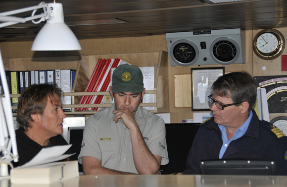 Hydrographer in Charge Andrew Leyzack, Ryan Harris, and Commanding Officer Stuart Aldridge during a survey logistics planning session on the bridge.