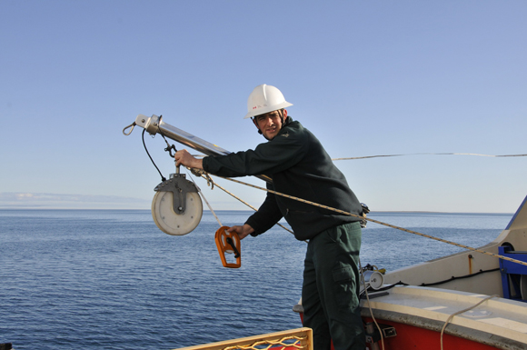 Ryan Harris measures the side-scan sonar towing configuration on the Kinglett.