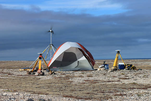 GPS reference station on an island in the search area with a remote satellite terminal for data transfer and battery bank in the tent. Solar panels and a wind turbine help supply power to the terminal