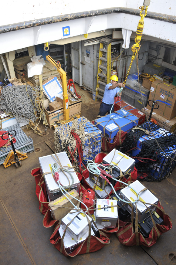 Seaman John Thomas unloads ROV gear and survey equipment in the forward hold.