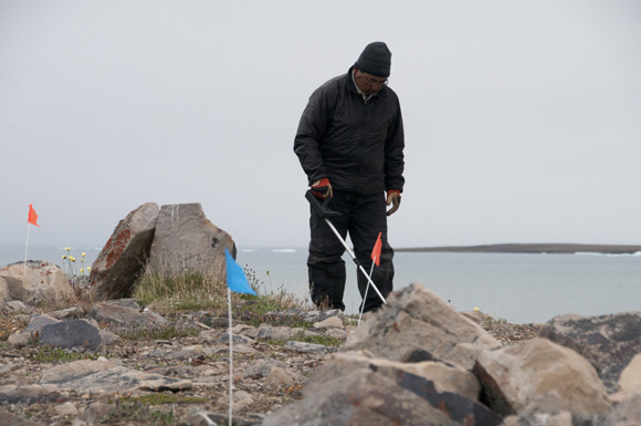 Mervin Joe operating a metal detector at the Paleoeskimo site