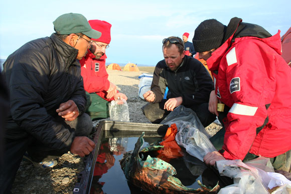 Archaeologists assess the condition of a piece of copper sheathing recovered from the wreck of HMS Investigator. From left to right: Mervin Joe, Marc-André Bernier, Henry Cary and Ryan Harris. Credit: John Lucas, Parks Canada