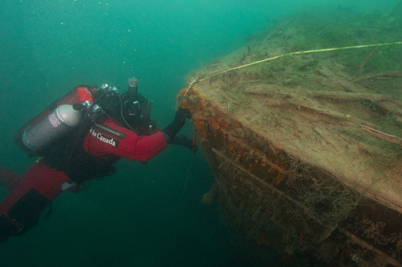 Archaeologist measuring dimensions of stem post on the bow of HMS Investigator.