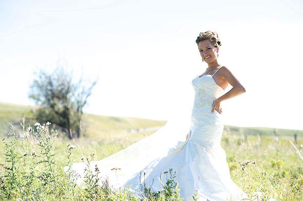 Bride poses by a country road