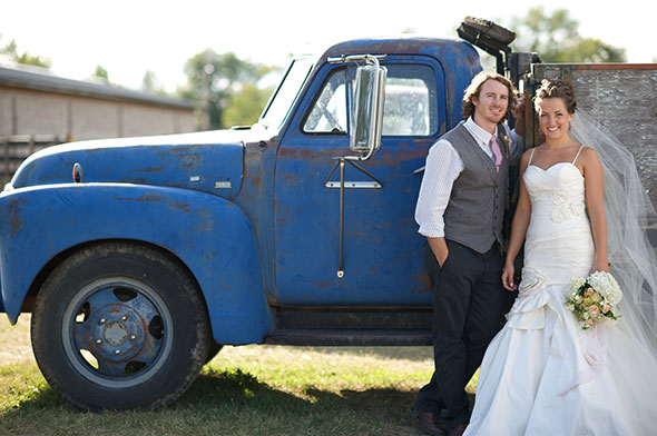 Wedding couple pose next to an old truck
