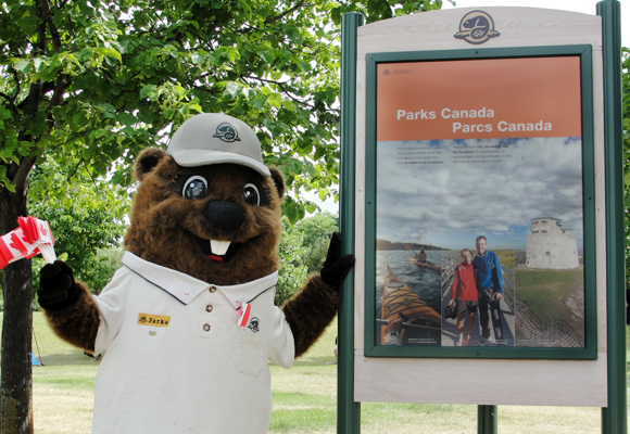 Parka, holding Canadian flags, poses in front of a Parks Canada poster at The Forks National Historic Site.