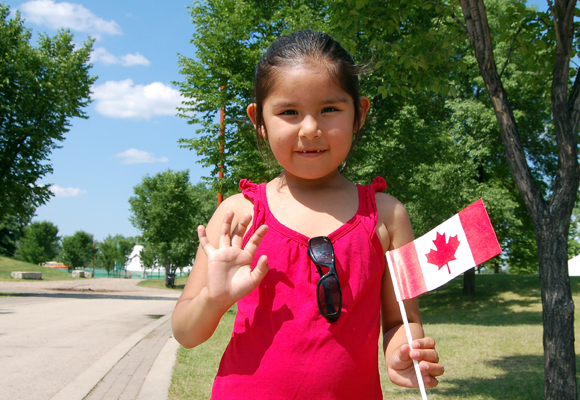 A young girl waving a Canadian flag at The Forks National Historic Site.