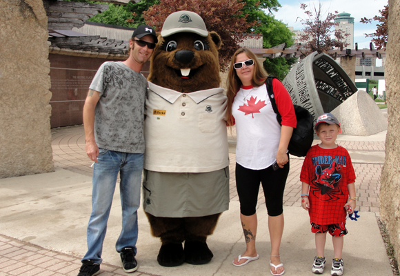 A couple and their young boy pose with Parka at The Forks National Historic Site.