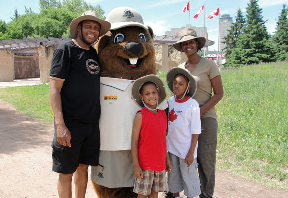 A couple and their two young boys pose with Parka at The Forks National Historic Site.