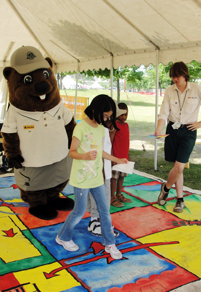 Kids playing the life-size board game with Parka and Parks Canada staff looking on.